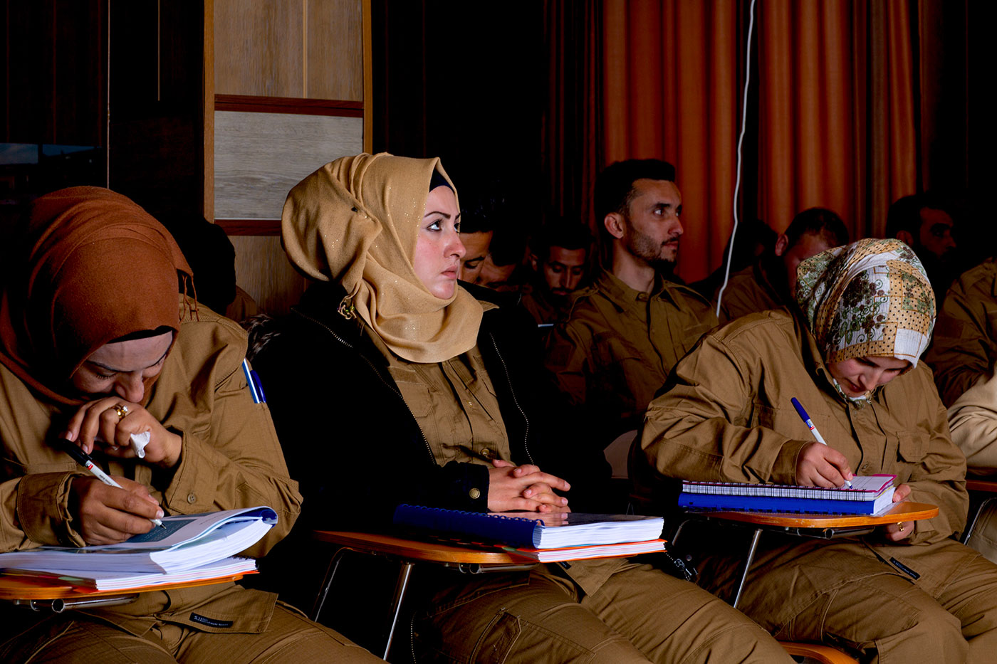 A group of men and women sitting, the women all wearing hijabs, they are listening and talking notes