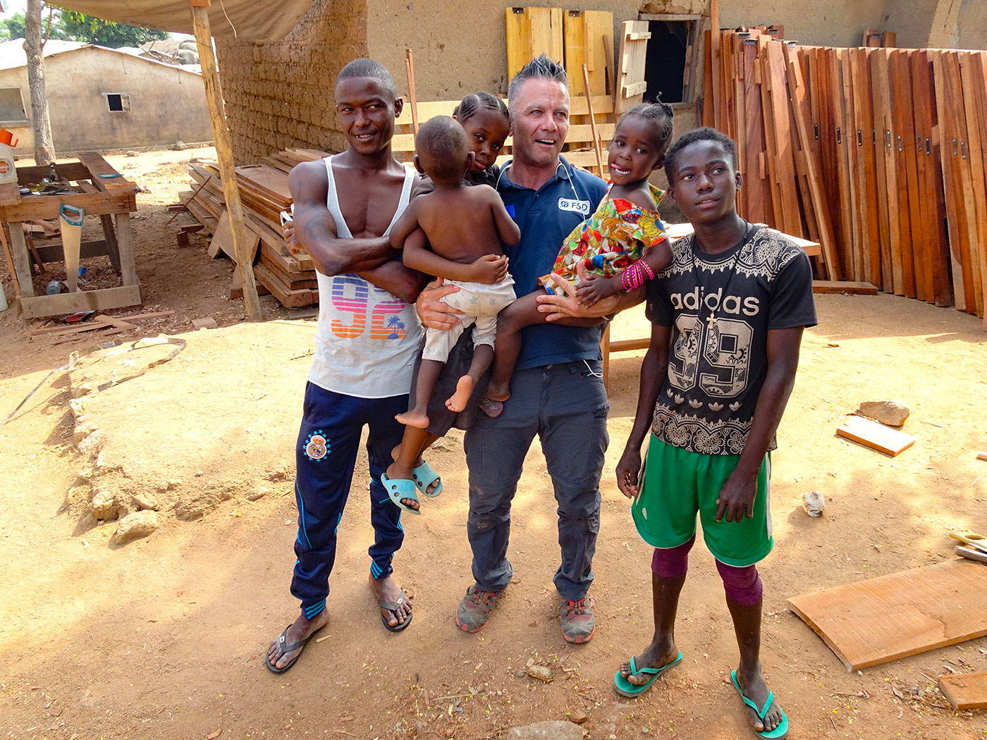 A man holding 3 kids and the other two man standing at his left and right
