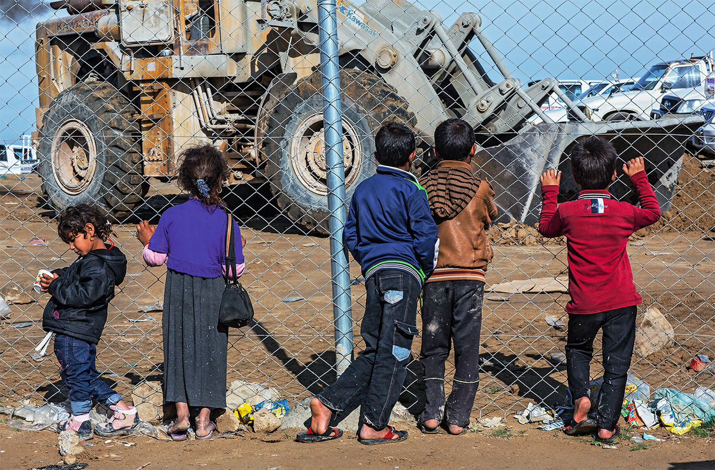 Back view of 5 children standing in front of a big iron net