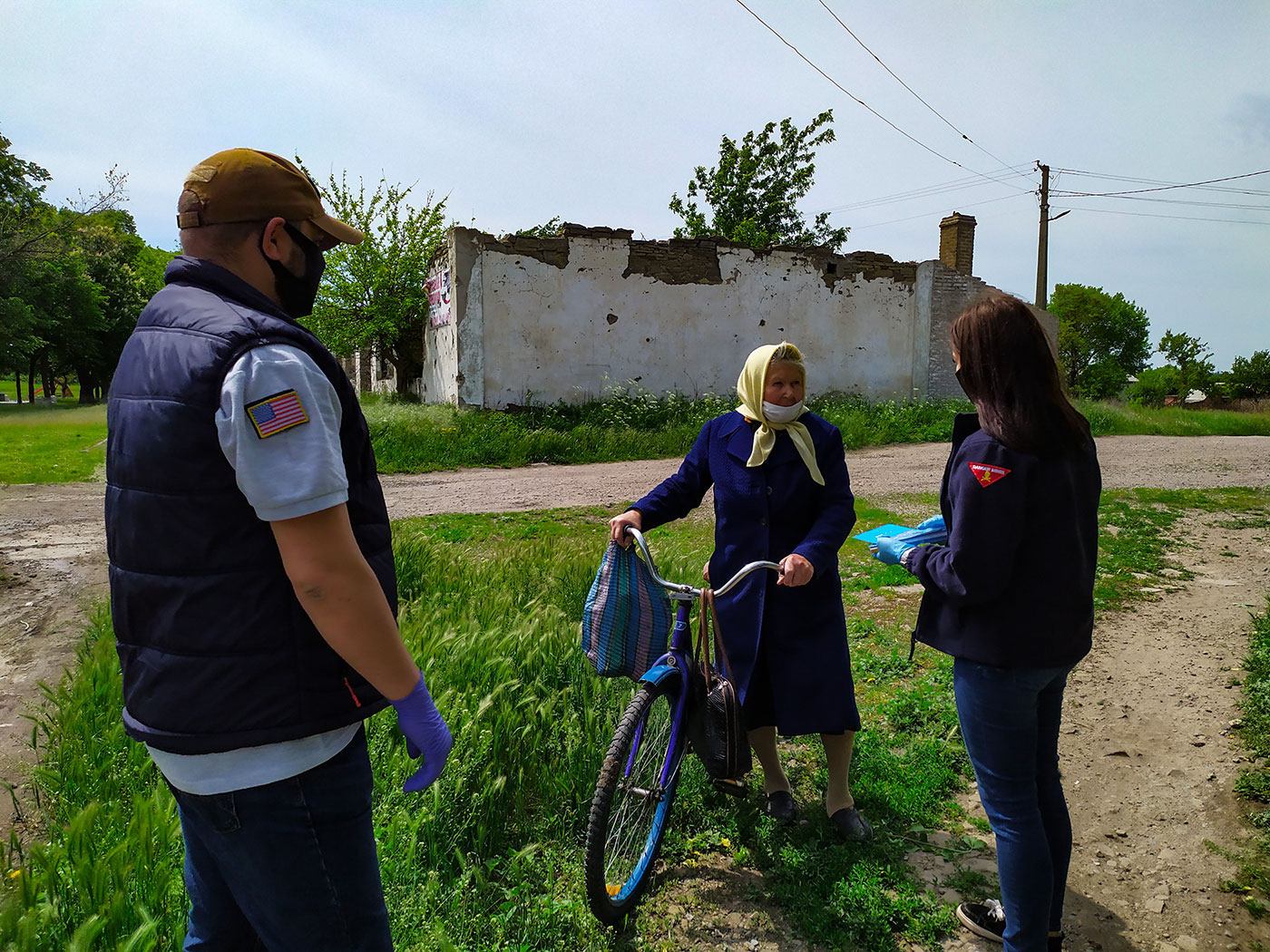 Two staff talking to an old lady with a bike