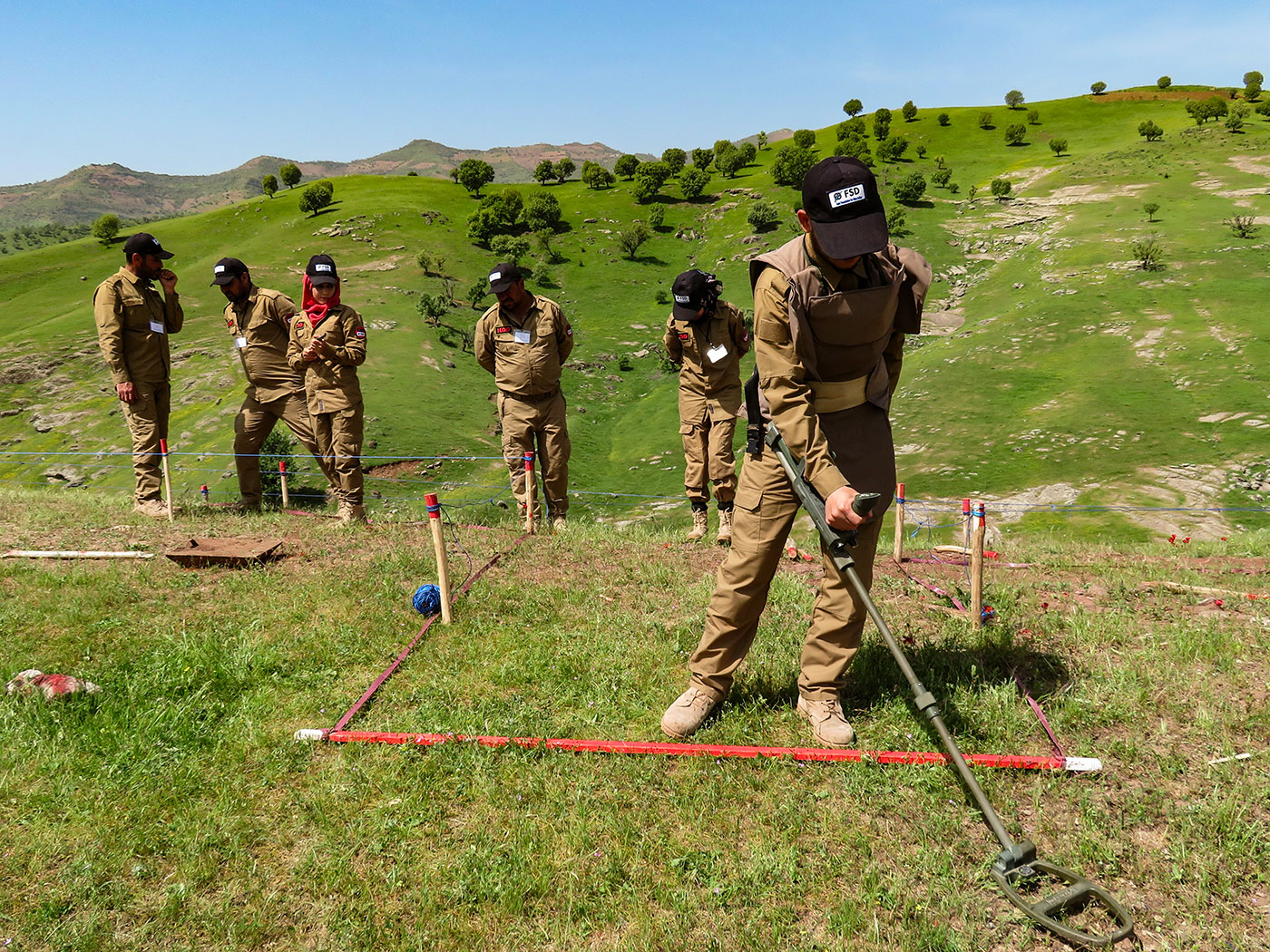 A group of FSD deminers working in green grass field
