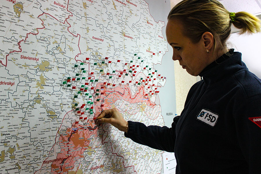 A woman wearing FSD uniform staning in front of a map full of flag pins