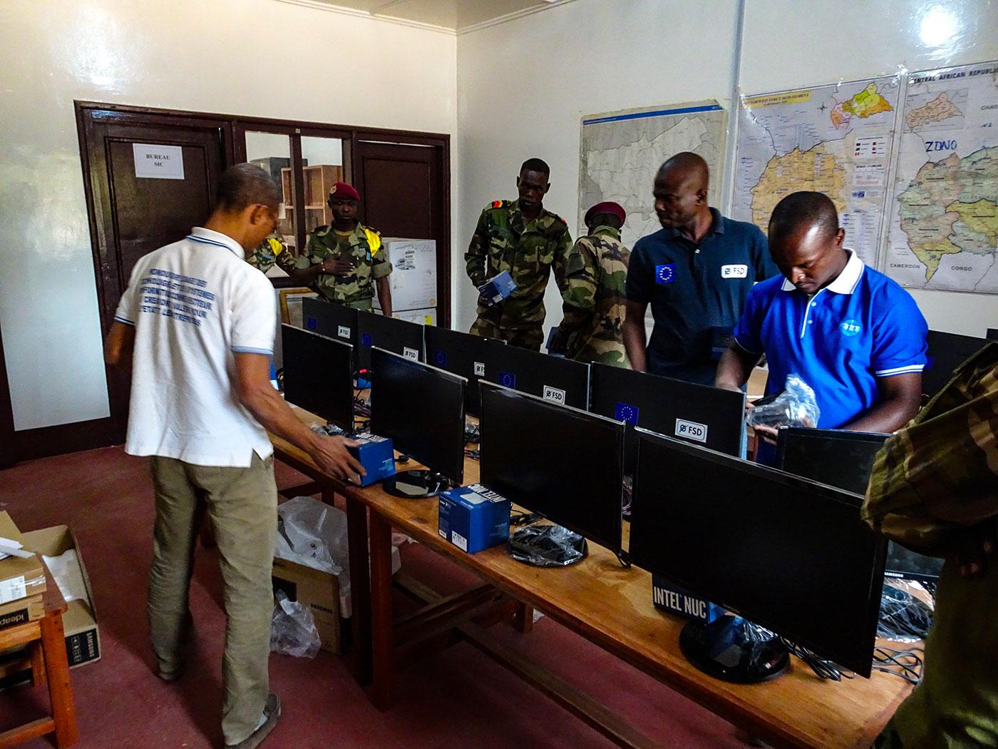 6 Männer stehen in einem Büro mit Computern