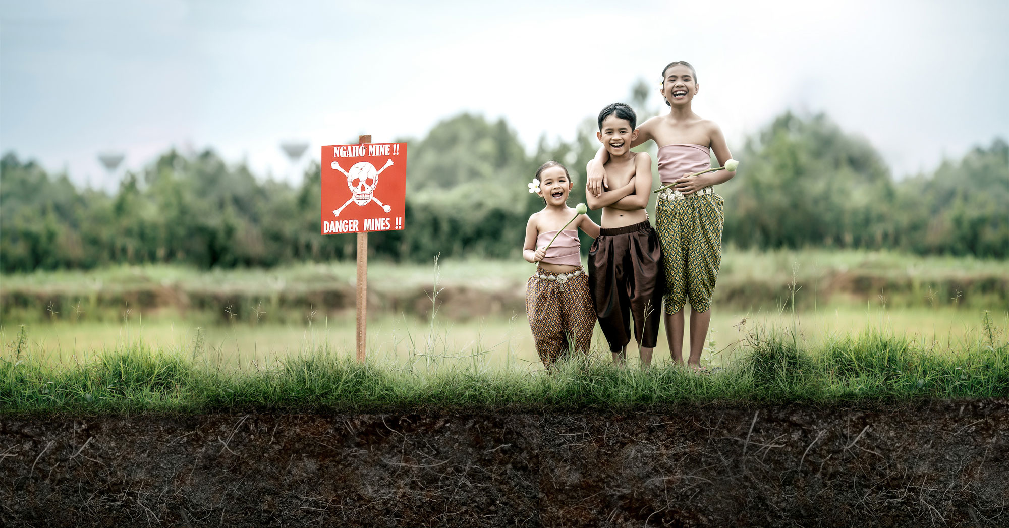 Three children laugh above a landmine