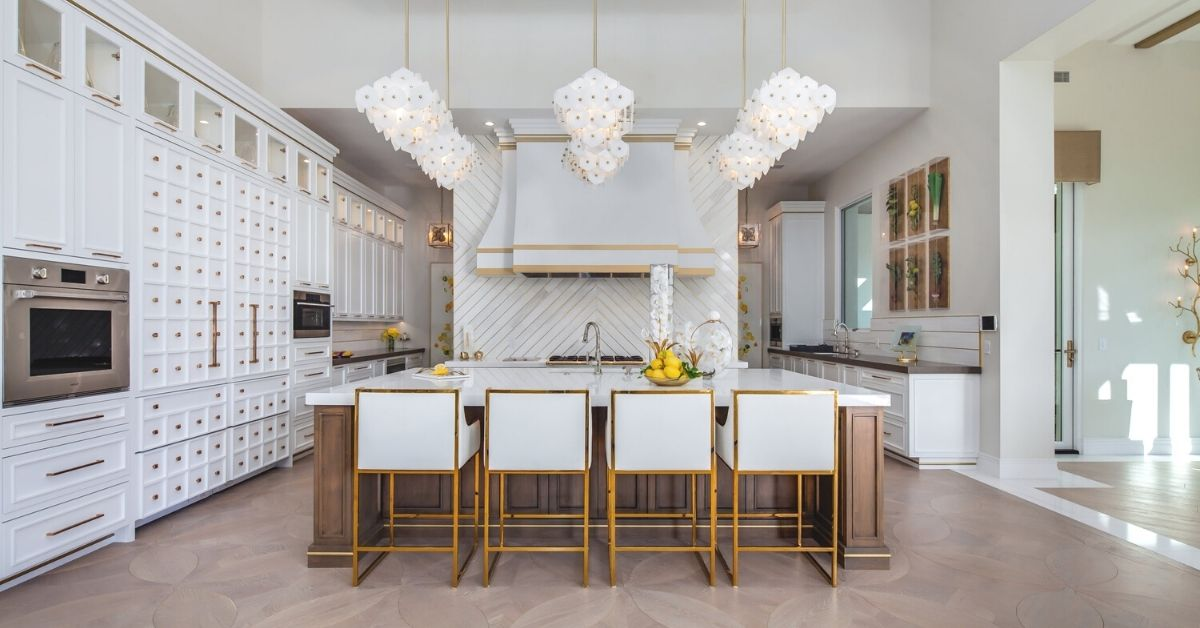 very large and luxurious kitchen with lots of white and gold details