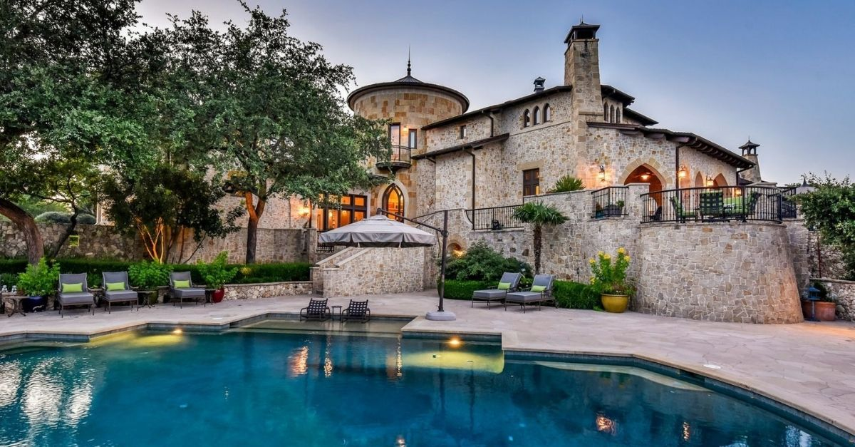 Castle looking house with light stone walls and sparkling blue pool