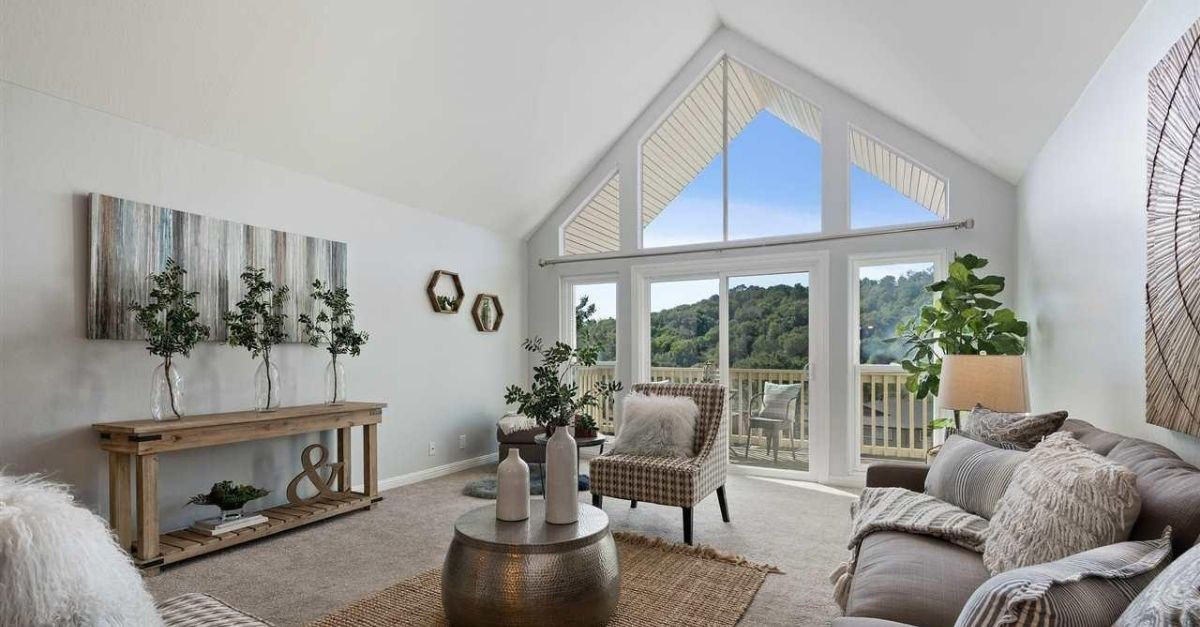 Interior of condo for sale in Moraga, California with large windows, staged furniture and balcony