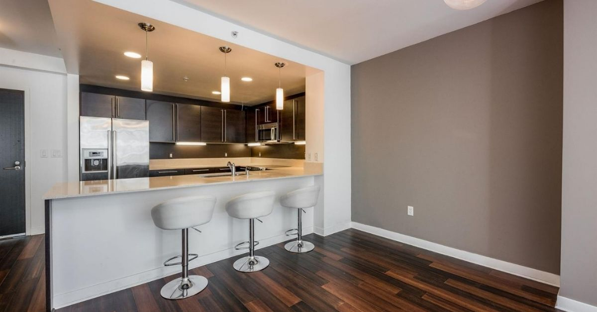 Kitchen in San Francisco condo with sub zero fridge and white bar stools