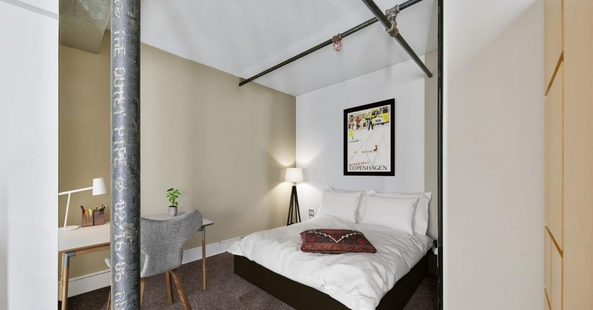 Bedroom with exposed pipe
