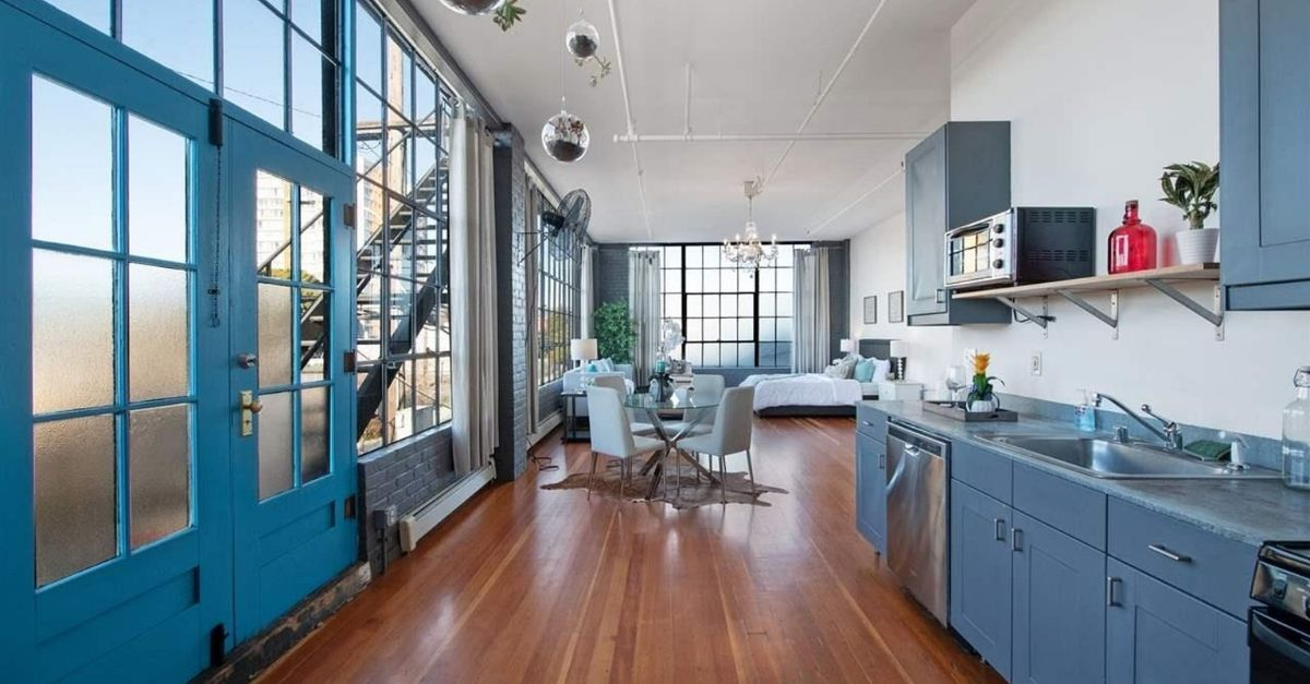 Blue kitchen with large warehouse windows