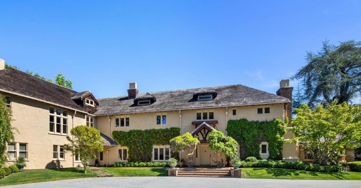 Exterior of country home with cream color facade and ivy
