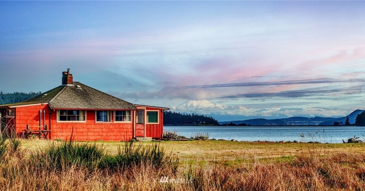 Waterfront red shingle style house with mountains in the background