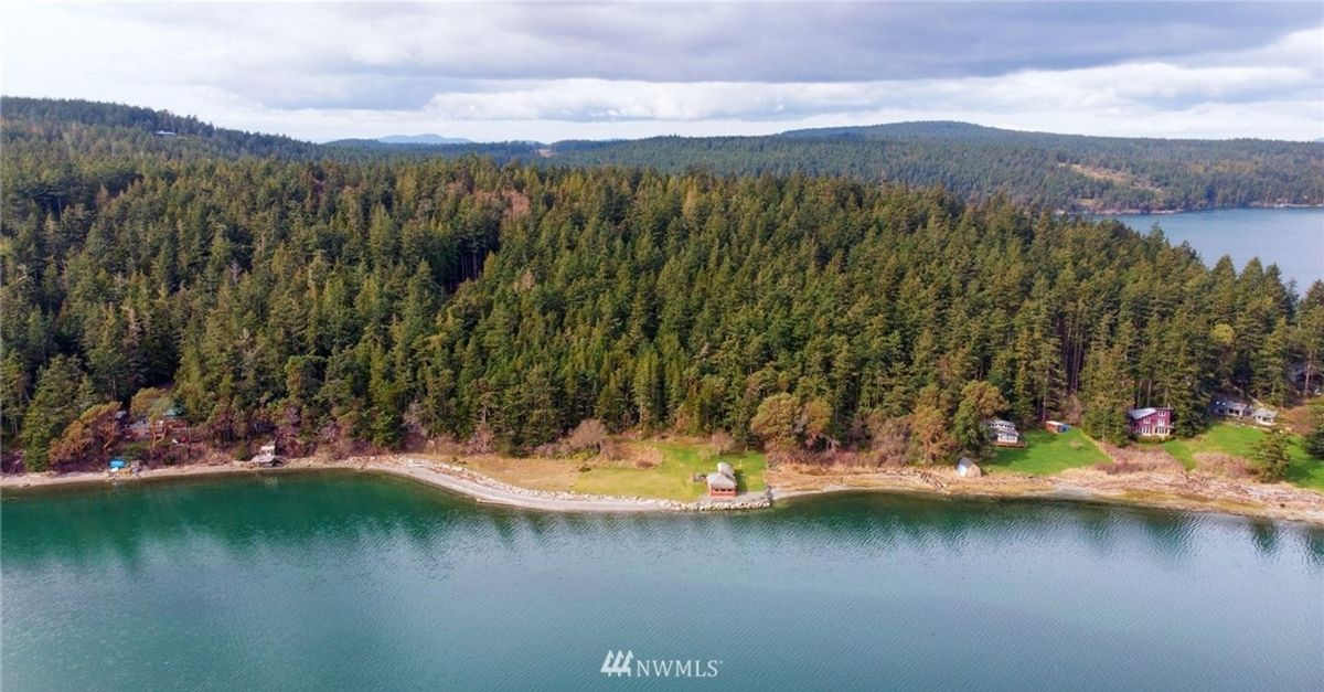 Aerial shot of waterfront red shingle style house surrounded by trees