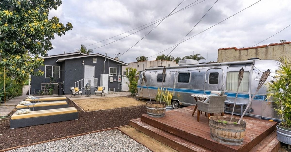 Grey house with silver airstream in the backyard
