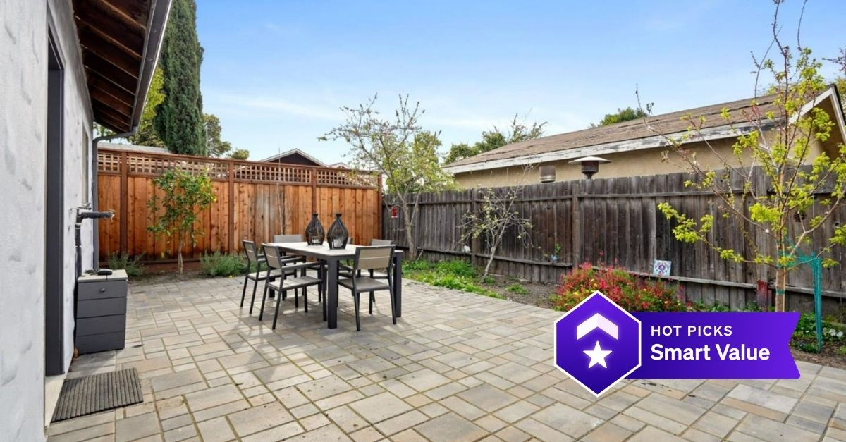 Fenced in backyard with table and chairs