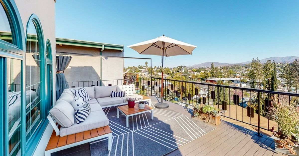Back patio with white sofa and umbrella overlooking Los Angeles