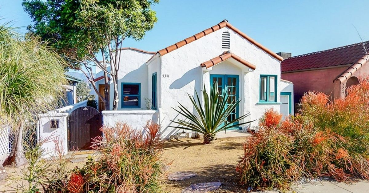 Spanish style home with white stucco facade, red tile roof, and blue door and windows details