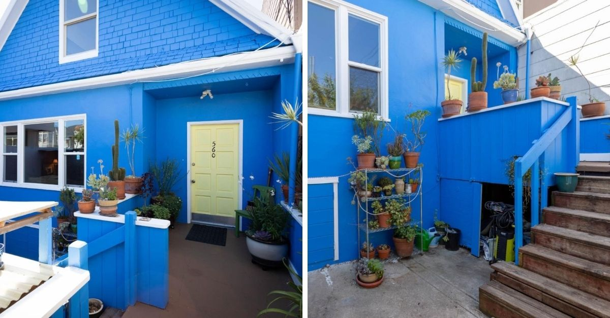 Blue Queen Anne Victoria home with plants out front and white paint details