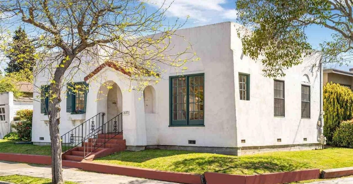 White Spanish style home with green border windows and a flat roof on a corner lot