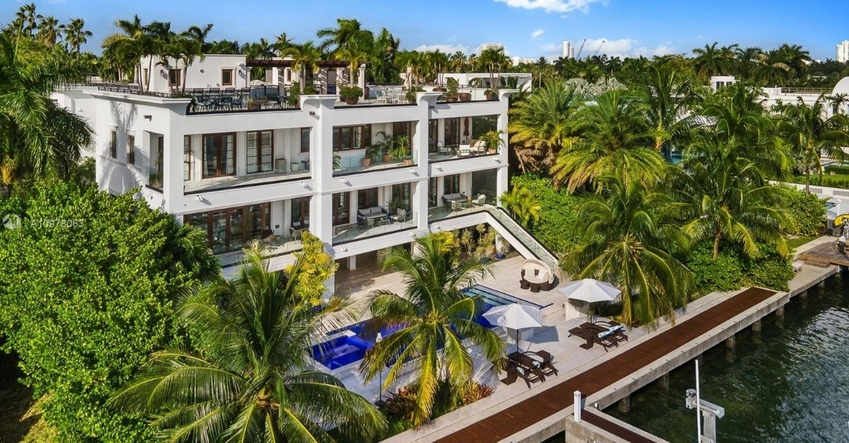 Oversized, modern white house on Miami waterfront with swimming pool and lots of lush and tropical trees outside