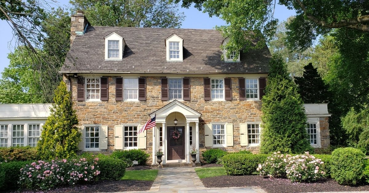 Beautiful colonial style home with light brown stone work and dark brown shutters