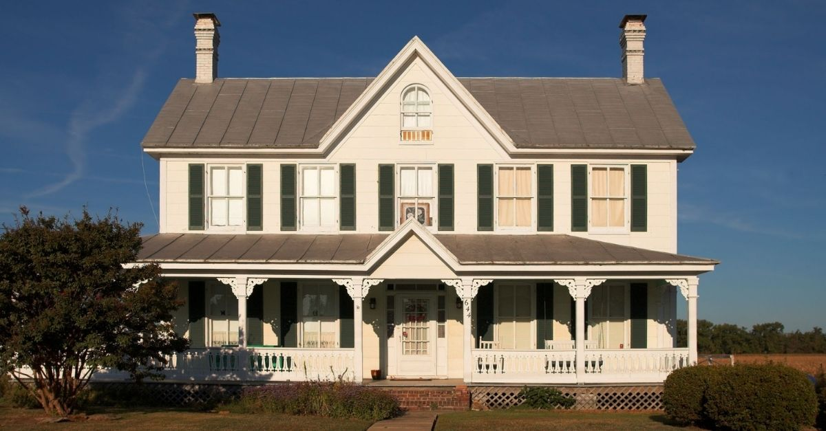French farmhouse with intricate woodwork along the front porch and dark green shutters