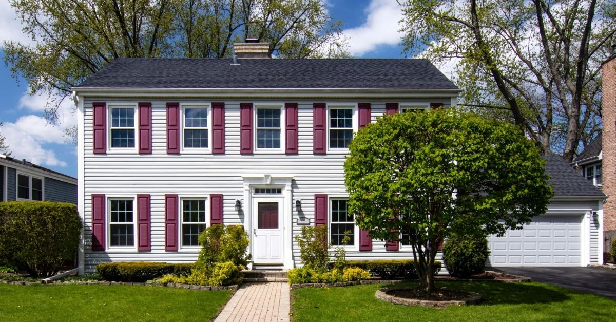 Saltbox colonial style house with white wood exterior and burgundy window shutters