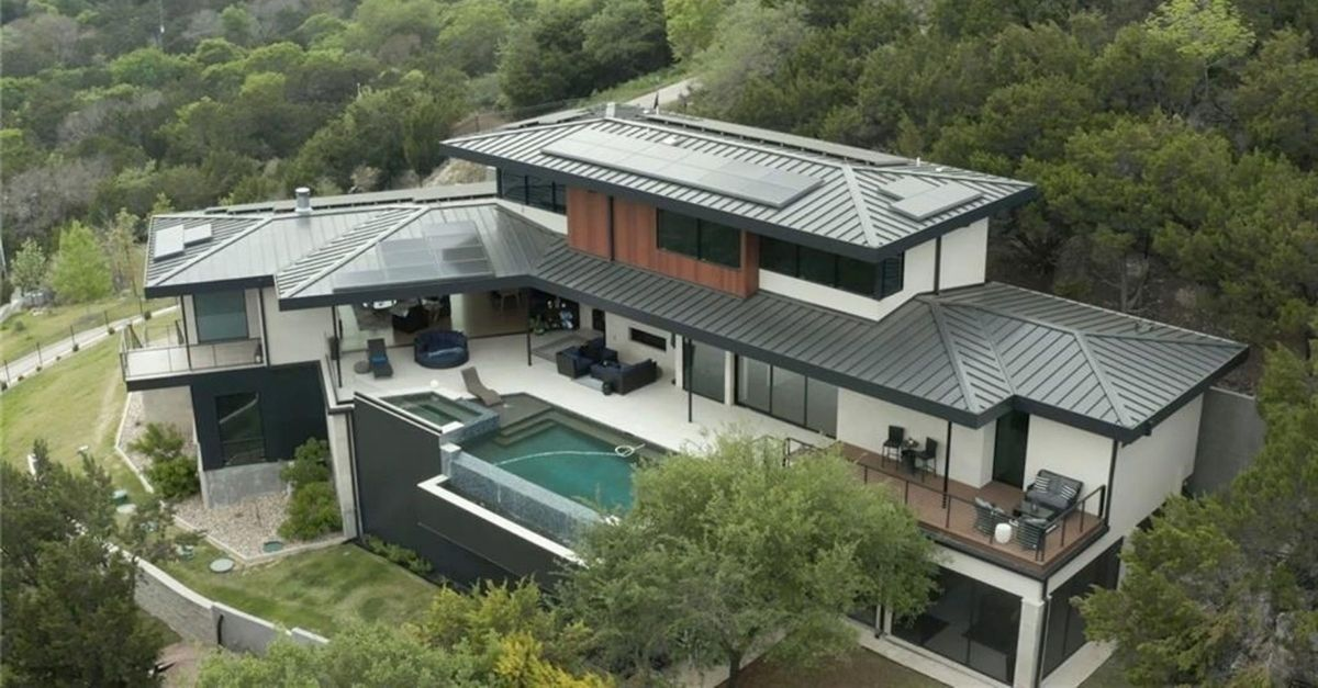 Aerial image of contemporary style home with solar panels on metal roof and infitnity edge pool and spa overlooking the garden