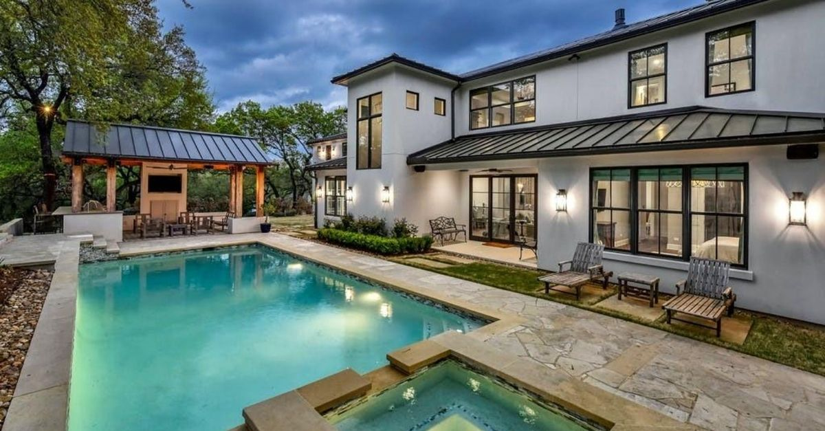 Contemporary style home with metal roofs and large windows behind a sparkling pool of a home for sale in Austin