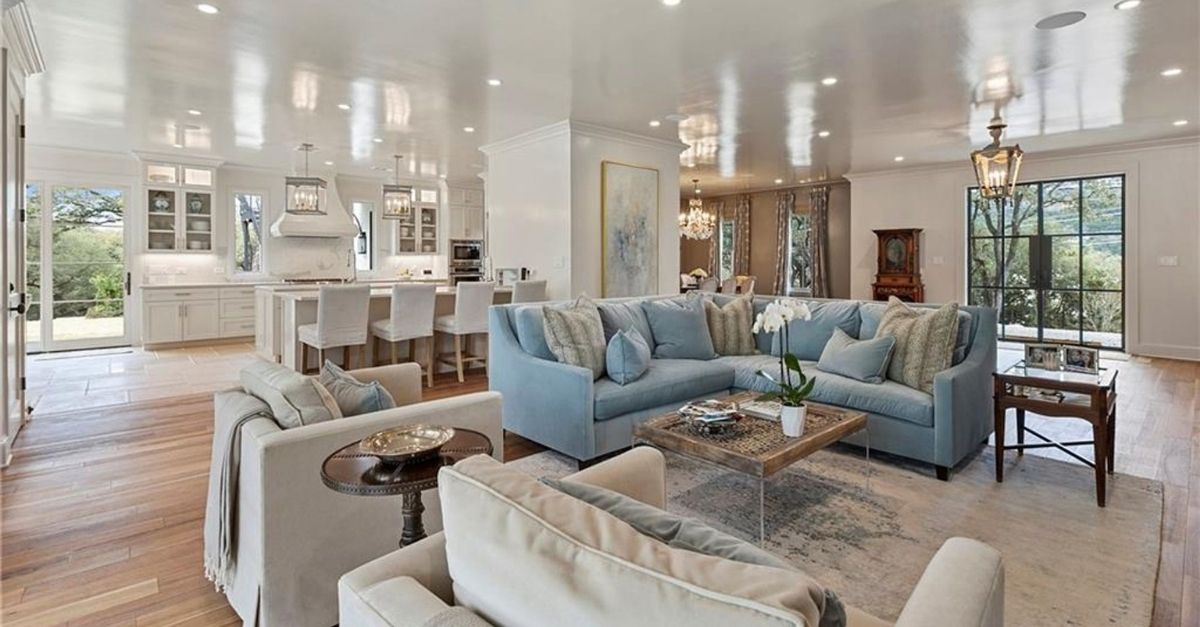 Open floor plan room with white marble kitchen in the background and living area in the front