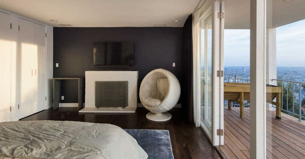 Bedroom with fireplace and black wall and circular chair at 8450 Carlton Way in Los Angeles