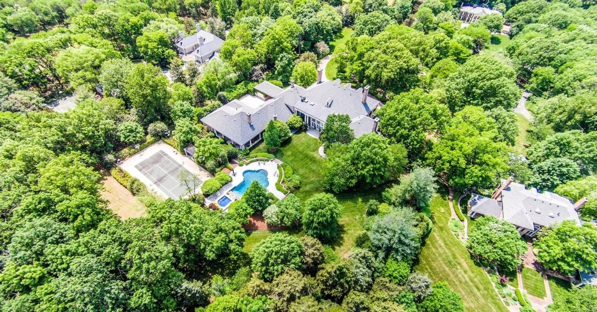 Aerial view of a grand Belle Meade, Nashville estate with vibrant green trees.