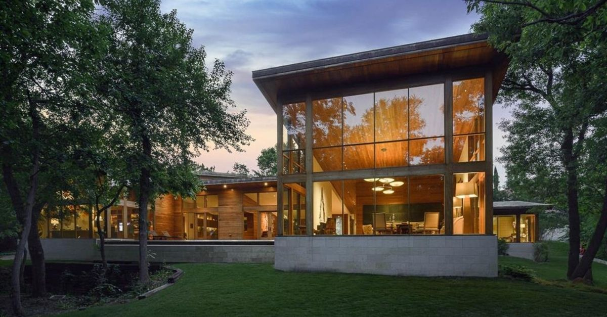 Exterior shot of grand house made of glass walls and wood