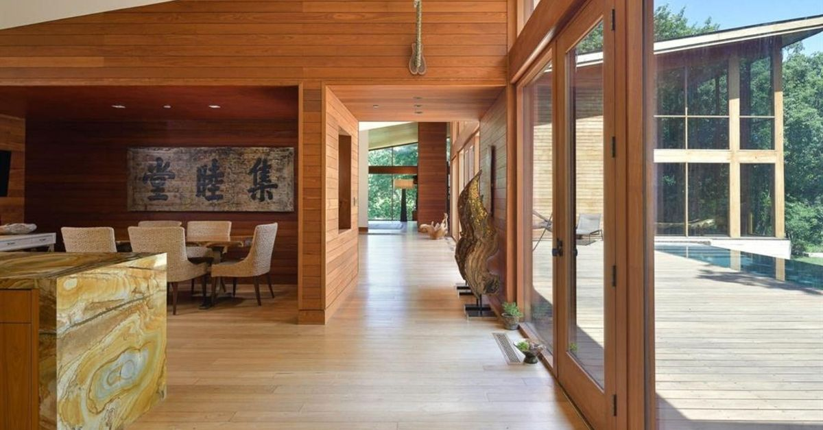 Hallway with wood walls and views of swimming pool through huge glass windows