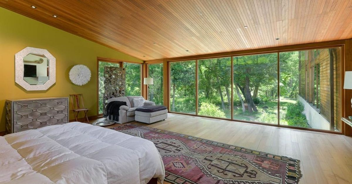 Beautiful bedroom with floor to ceiling windows and lush trees outside