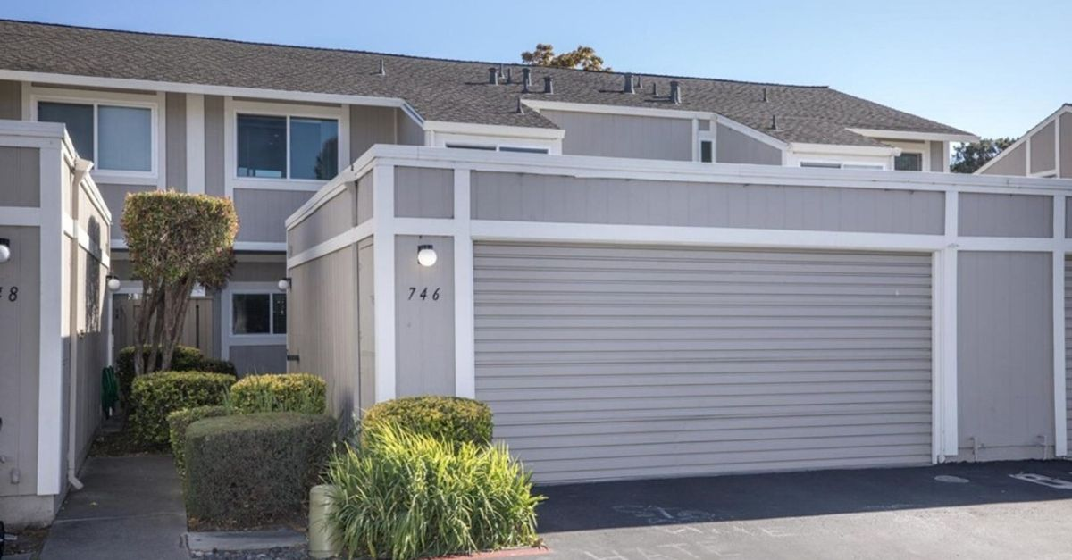 Grey attached townhouse with a large garage in front