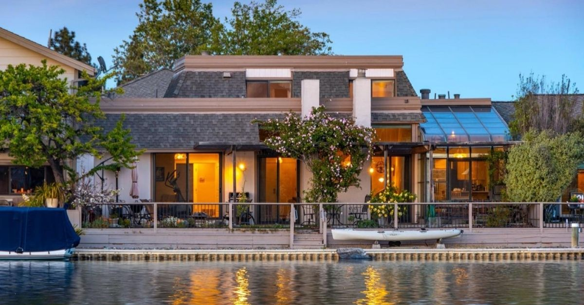 Beautiful glass house on the waterfront with glowing yellow lights inside and pretty plantst