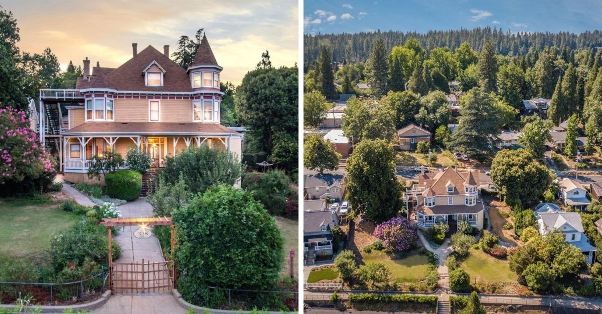 Beautiful tan colored Queen Anne style home surrounded by houses and trees
