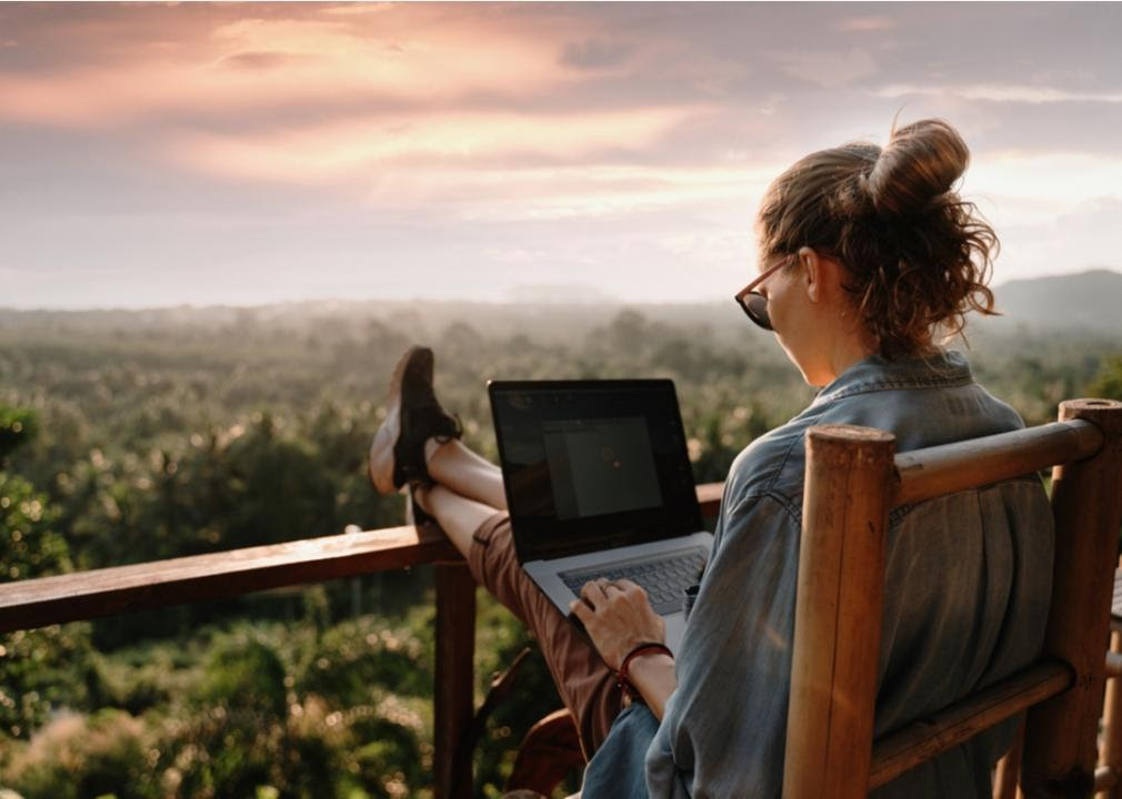 Woman on laptop overlooking green space