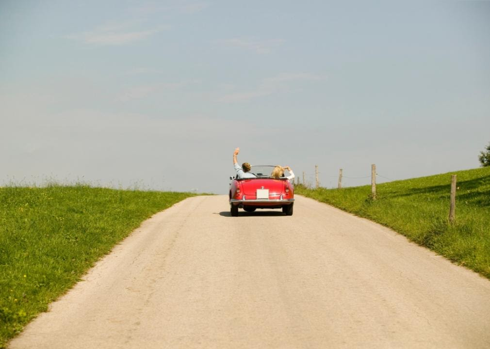 Old, red retro convertible driving on dirt road