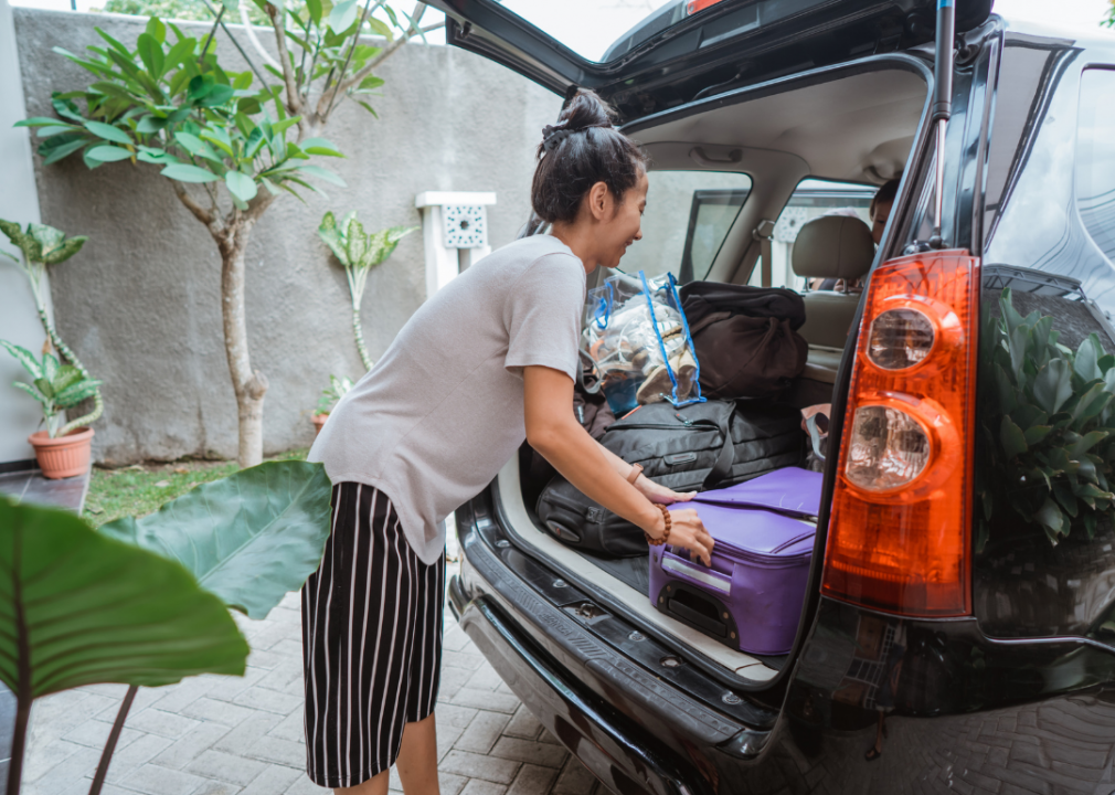 Woman loading car trunk with suitcase