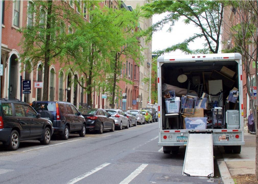 Moving truck on street filled with household items