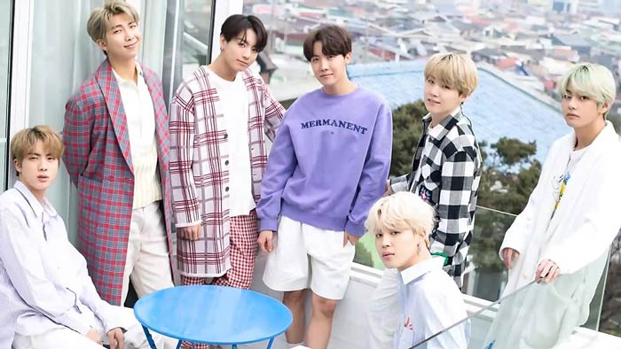 The band BTS sitting posing on a balcony with a city view behind them