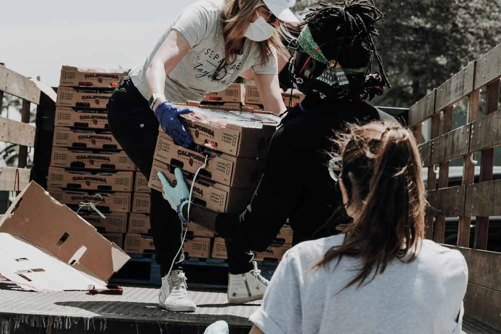 A woman wearing a face mask stands on the back of a truck and hands a volunteer a box of produce