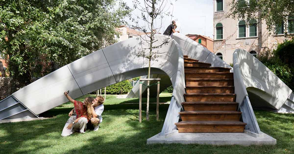 A small unique bridge is sitting in the middle of a park. It's concrete and a couple takes a selfie in front of it. Its stairs are made of wood.