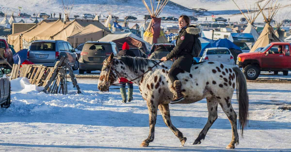 Young native woman rides a white and brown horse through a snow-covered parking lot/campground