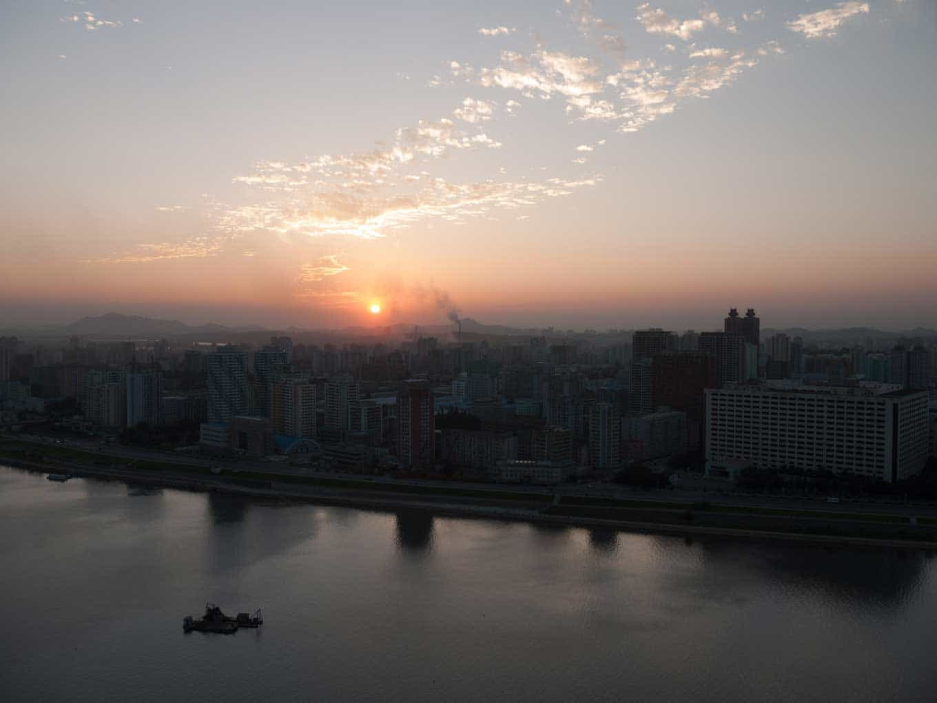 View of Pyongyang - short skyscrapers, a sunrise/sunset - a singular boat on the water