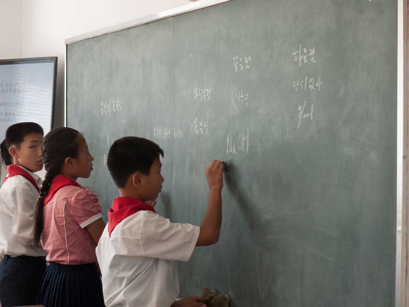 Two boys and one girl stand at blackboard in their school uniforms