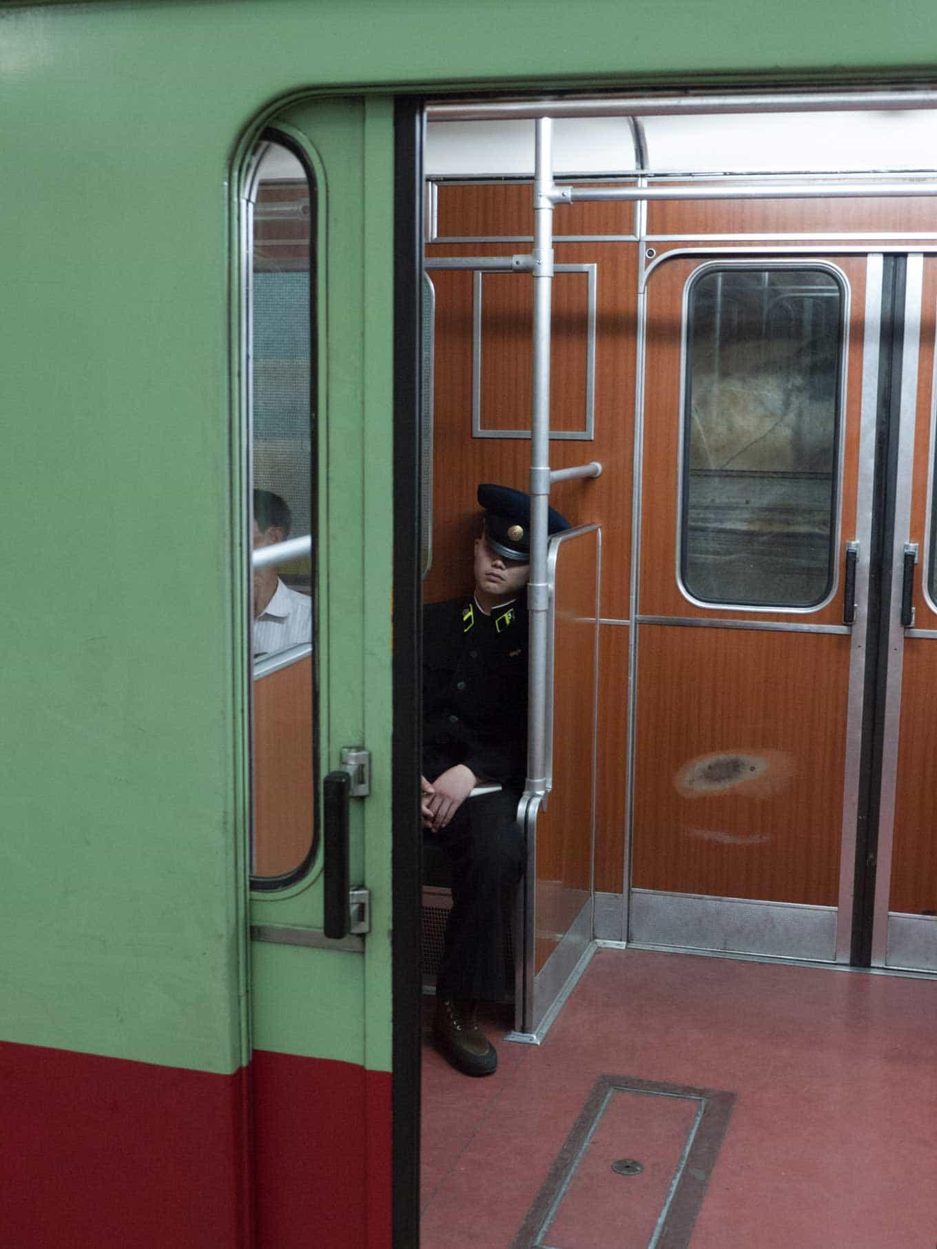 North Korean sleeps in their uniform on the public transit subway system in North Korea Pyongyang