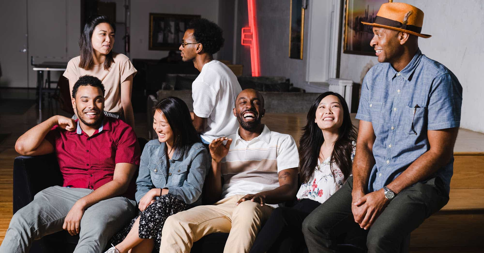 A group of Black, Asian, and Latinx friends smile and laugh on a couch in a diverse stock photo from TONL